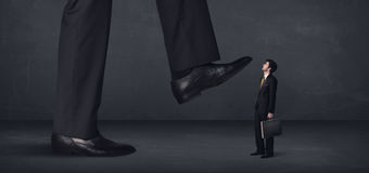 Giant person stepping on a little businessman concept Stock Photography
