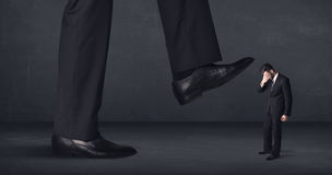 Giant person stepping on a little businessman concept Royalty Free Stock Image
