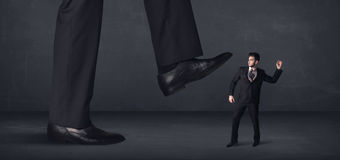 Giant person stepping on a little businessman concept Royalty Free Stock Photography