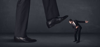 Giant person stepping on a little businessman concept Royalty Free Stock Photo