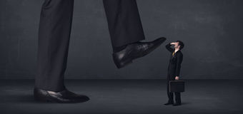 Giant person stepping on a little businessman concept Stock Image