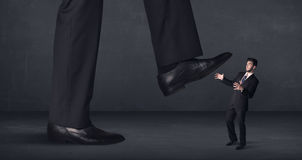 Giant person stepping on a little businessman concept Stock Photos