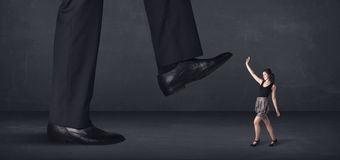 Giant person stepping on a little businesswoman concept Royalty Free Stock Photo