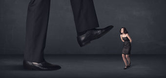 Giant person stepping on a little businesswoman concept Stock Image