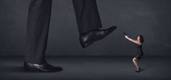 Giant person stepping on a little businesswoman concept Stock Photos
