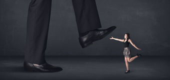 Giant person stepping on a little businesswoman concept Royalty Free Stock Photography