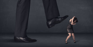 Giant person stepping on a little businesswoman concept Royalty Free Stock Images
