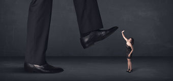 Giant person stepping on a little businesswoman concept Stock Photography