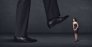 Giant person stepping on a little businesswoman concept Stock Images