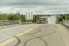 Giant red dump truck makes way down to the trans canada on road with tire markings. Giant red dump truck makes it way down to the trans canada on road with tire Stock Images