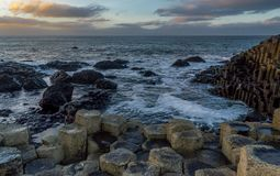 Giant`s Causeway, North Ireland, UK during winters. The fierce waves batter the iconic coastline of North Ireland. In a distance the sky is lit with sun rays stock photos