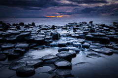 Giant's Causeway after sunset. The Giant's Causeway  at night as the last light of the setting sun appears over the horizon, in Northern Ireland Stock Photo
