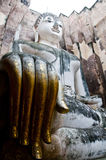 Giant seated Buddha. Giant statue of a seated Buddha with tapered fingers covered with gold leaves in Sukhothai Historical Park - Thailand Royalty Free Stock Photos