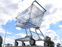 Giant shopping cart. A giant shopping cart in front of a shopping center. there are light chains along the outer lines of the cart and around the wheels. must royalty free stock image