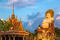 Giant happy buddha Samui. Giant smiling or happy buddha statue in Wat Plai Laem Temple, Samui, Thailand in a summer day royalty free stock images