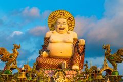 Giant happy buddha Samui. Giant smiling or happy buddha statue in Wat Plai Laem Temple, Samui, Thailand in a summer day royalty free stock photos