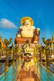 Giant happy buddha Samui. Giant smiling or happy buddha statue in Wat Plai Laem Temple, Samui, Thailand in a summer day stock image