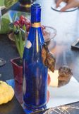Giant snail Achatina crawling on blue bottle in the background of hyacinth and grapes royalty free stock photos