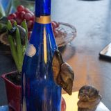 Giant snail Achatina crawling on blue bottle in the background of hyacinth and grapes stock image