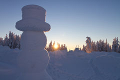 Giant snowman in winter wonderland. Giant snowman overlooking winter wonderland in sunset Stock Photography