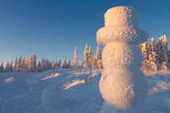 Giant snowman in winter wonderland. Giant snowman overlooking winter wonderland in sunset Royalty Free Stock Photos