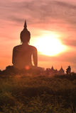 Giant statue of Buddha in the morning light at Wat Muang, Angthong, Thailand. ANGTHONG, THAILAND - JUNE 19: Unidentified woman rides her bicycle to Wat Muang Stock Images