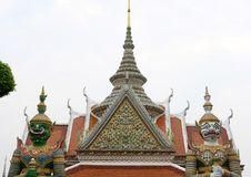 giant statue & sculpture on asian temple. buddhist building encrusted with glazed porcelain tiles & seashell at wat arun royalty free stock photo