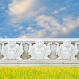 Giant statue at temple wall near yellow flower field Stock Photo