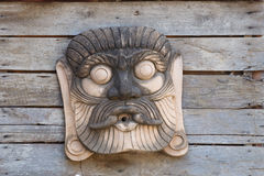 Giant statue on wooden wall Stock Image