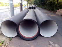 Giant steel tubes are placed on the sidewalk. Stock Photo