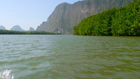 The giant steep rock rises above the rainforest. View from the longtail boat. Picturesque seascapes with mangrove forests under the blua tropical sky of the stock footage