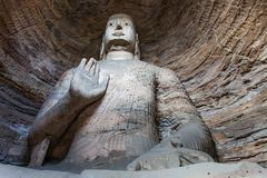 Giant Stone Buddha. Giant Buddha carved from stone, housed in a cave at the Yungang Grottos Stock Photography