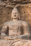 Giant Stone Buddha. Giant Buddha carved from a reddish brown stone, housed in a cave at the Yungang Grottos Stock Images
