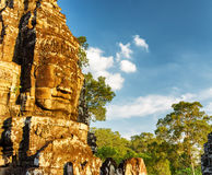 Giant stone face of ancient Bayon temple, Angkor Thom, Cambodia. Mysterious giant stone face of ancient Bayon temple in Angkor Thom in evening sun. Siem Reap Royalty Free Stock Photo