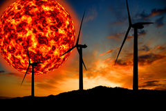 Giant sun and wind turbines. Illustrated giant flaring sun at sunset with wind turbines in silhouette Stock Images