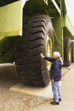 Giant Titan mining haul truck. Woman looking at the giant tires on a Titan mining haul truck on display at Sparwood, BC, Canada Stock Image