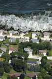 Giant Tsunami Tidal Wave Natural Disaster. Artist rendition of a tsunami or giant tidal wave. The ocean comes crashing into a residential area of houses and stock photography