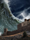 Giant tsunami waves crashing old fortress. Apocalyptic dramatic background - giant tsunami waves crashing old fortress, tower. Stormy sky with lightning royalty free stock image