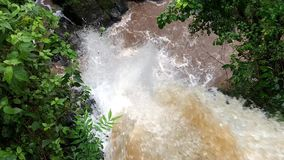 Waterfall in Iguazu Falls view from above. Giant water jet falling surrounded by green vegetation. Brown waters belonging to the Iguazú River, in Cataratas stock footage