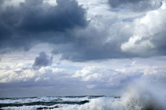 Storm Wave. A giant wave raising above the sea's water surfaced, its surf scattered by the strong wind under the heavily overcast winter sky Stock Image