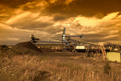 A giant wheel excavator in brown coal mine at sunset Stock Photo