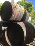 Giant whiskey barrels stacked atop. Each other, on a sunny courtyard, with green trees protruding behind. Barrels such as these were used for brewing/ageing stock images