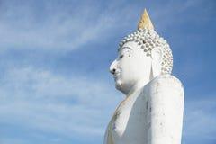 Giant white buddha statue under blue sky stock images