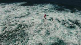 Giant white foam waves crashing as windsurfer glides in dark deep blue ocean in stunning 4k aerial drone camera seascape. Giant white foam waves crashing as stock video footage