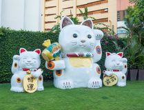 Giant white Japanese lucky cat sculpture in a group of three family cat at gateway Ekamai shopping mall. royalty free stock image