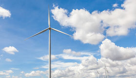 The giant wind turbine stands against cloudy blue sky background Stock Images
