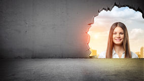 A giant woman`s face looking from outside into a room through a large uneven opening in the wall. Breakthrough. New business horizons. Future growth Royalty Free Stock Photos