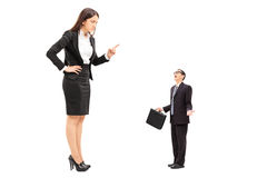 Giant woman threatening a tiny businessman Royalty Free Stock Images