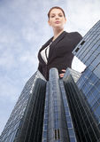 Giant young businesswoman standing behind office building Royalty Free Stock Photos