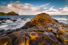 Giants Causeway sunrise. Sunrise view at Irish giant causeway vulcanic formation with rainbow nearby Stock Images